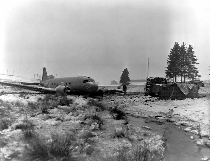 The pilot of a C-47 cargo transport crash lands safely after having dropped supplies to elements of the 101st Airborne Division which has successfully repulsed all attempts to capture the besieged city of Bastogne Belgium 30 December 1944