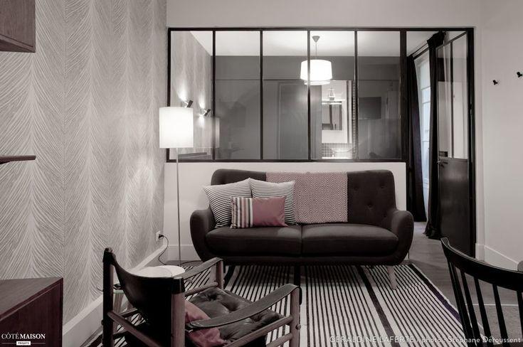 Un salon aux tons sombres, réhaussé par une verrière.