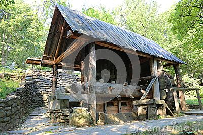 Ancient watermill surrounded by wall of river stones.