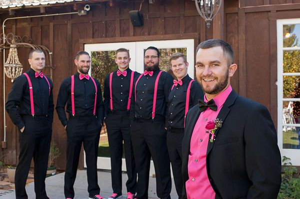 Black & Pink Groomsmen Attire: For a more casual wedding, the groom and groomsmen sported both elegant and casual wedding accessories in the wedding's hot pink color palette. Groomsmen attire included black button-down shirts, hot pink suspenders, hot pink bow ties and black Converse wedding shoes with hot pink shoe laces. The groom wore a pink button-down shirt with a black bow tie, a black suit and hot pink floral boutonniere.
