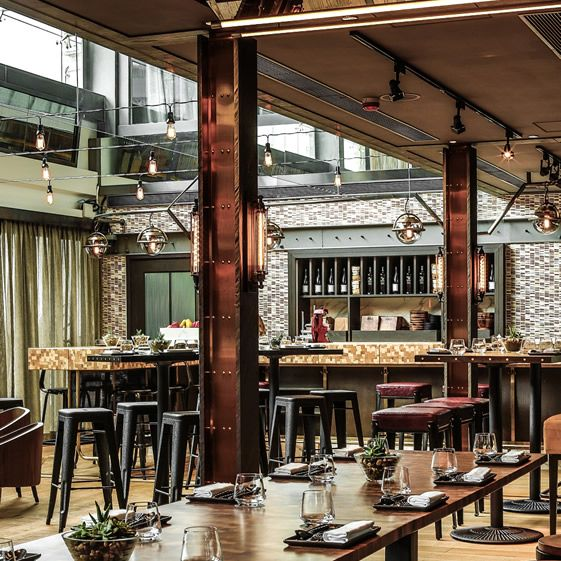 There are some earthy themes within a generally shiny place; the flooring is composed of outlying sections of reclaimed wood planks and baked brick in the middle, and the influence of the Mediterranean cuisine is echoed in the colour palette which uses olive green and dark timber...