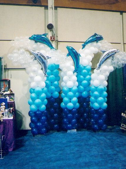 Ocean colored balloon columns with dolphins on top. I can almost hear the waves.