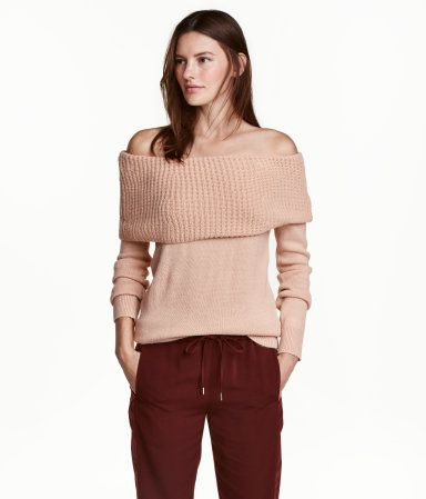 Zwart. Een gebreide trui van zachte kwaliteit met een brede, ribgebreide, omslag bovenaan die de schouders onbedekt laat. De trui heeft een ribgebreide