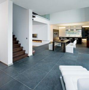 Leisteen vloer in moderne villa. In de woonkamer van deze moderne villa ligt een prachtige leisteen vloer. Leisteen heeft een natuurlijke warme uitstraling en is praktisch onverwoestbaar. Echt een vloer die een leven lang meegaat! KROON Vloeren in Steen
