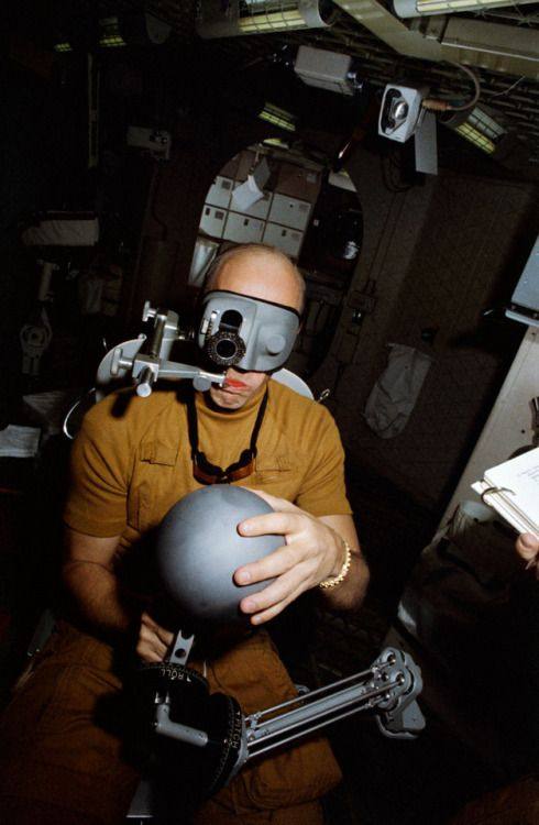 """March 1, 1973 – Astronaut Pete Conrad tries the """"Human Vestibular Function, Experiment M131"""" during Skylab mission training at the Johnson Space Center: """"The reference sphere with a magnetic rod is used by the astronaut to indicate body orientation..."""