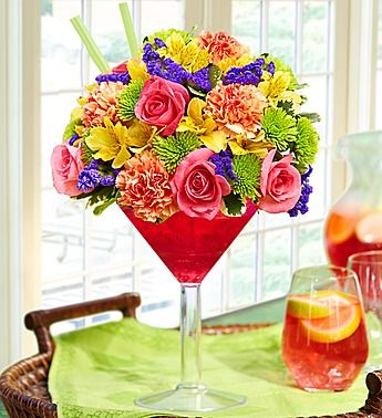 Sangria Bouquet™. Spice things up with our fresh floral version of the popular wine punch. Our florists gather a kaleidoscope of roses, carnations, alstroemeria, poms and statice and hand-arrange them with in a chic acrylic martini glass to resemble a glass of sangria. Send one today and you'll have them dancing the samba in no time. Save 20% with the coupon code ABENITY at http://www.1800flowers.com.