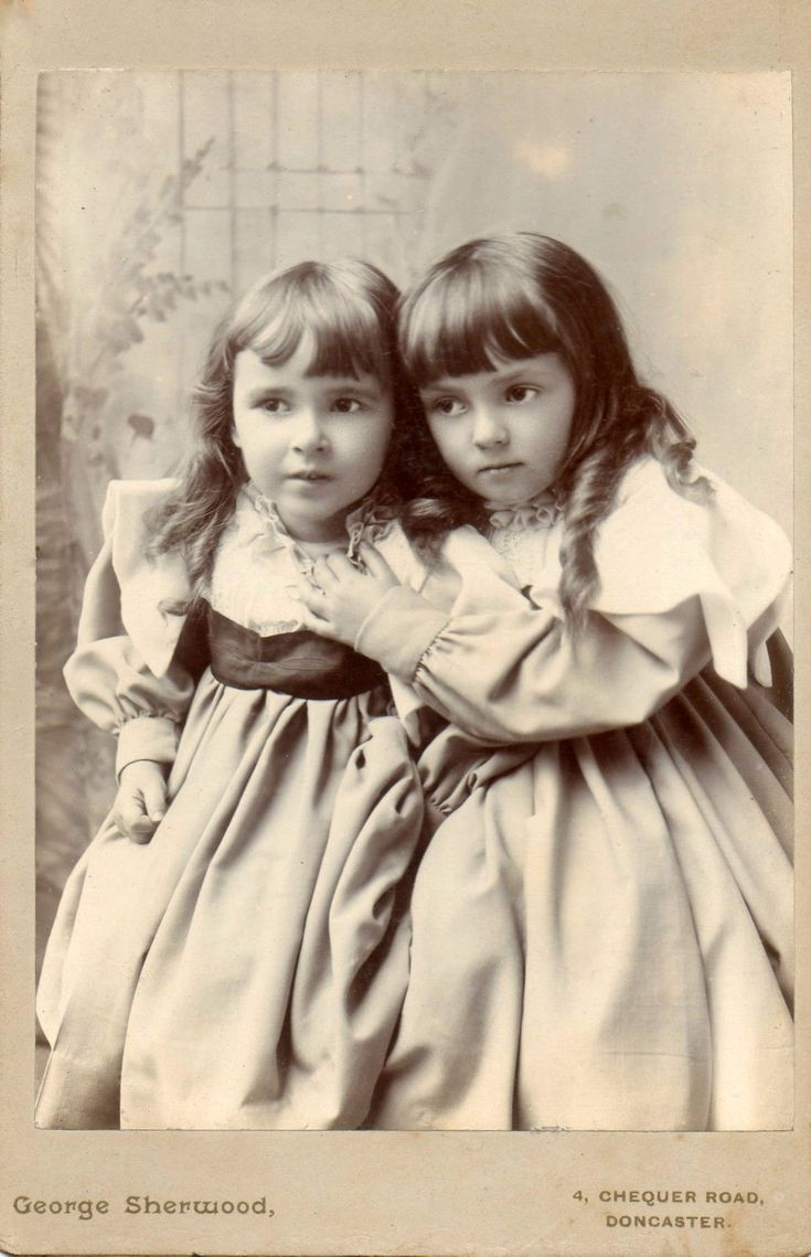 Charming little sisters. Their moods are so different: the one on the left is full of anticipation, while the one on the right exudes solemn resignation.