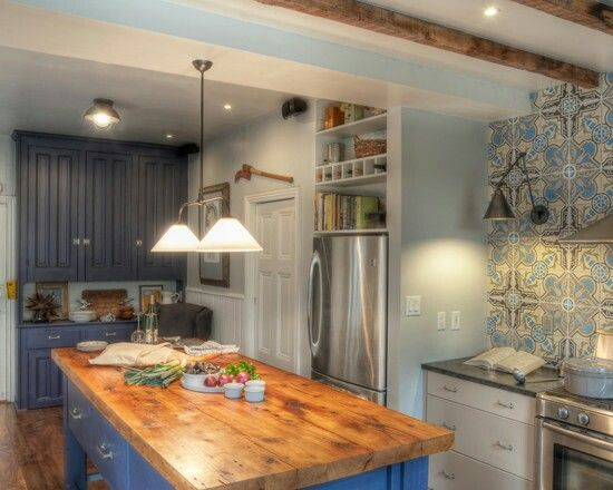 Beautiful mosaic tile backsplash to tie in the different shades of blue paint colors w butcher block island and stainless steel appliances.