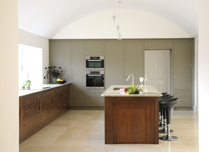 Walnut additions to this bespoke kitchen compliment the olive green cabinetry to give this kitchen a contemporary finish
