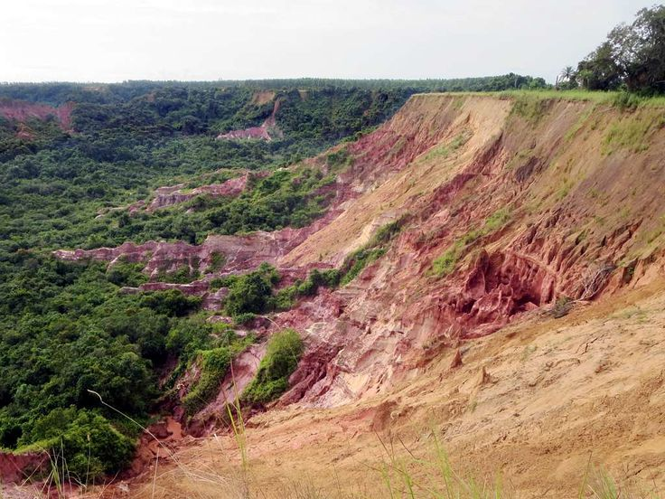 The Diosso Gorge north of Pointe-Noire, Republic of Congo, features red rock cliffs created by erosion.