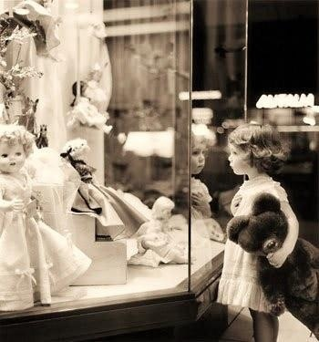 Looking through the store window and thinking maybe Teddy needs a friend!  (Date/location/photographer unknown).