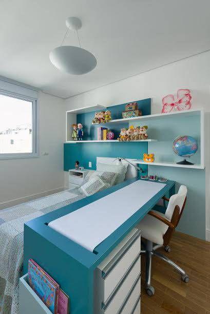 Bancadas de estudos azul petróleo e branca. Tem o formato de ilha e está em um quarto, ao lado da cama da moradora.