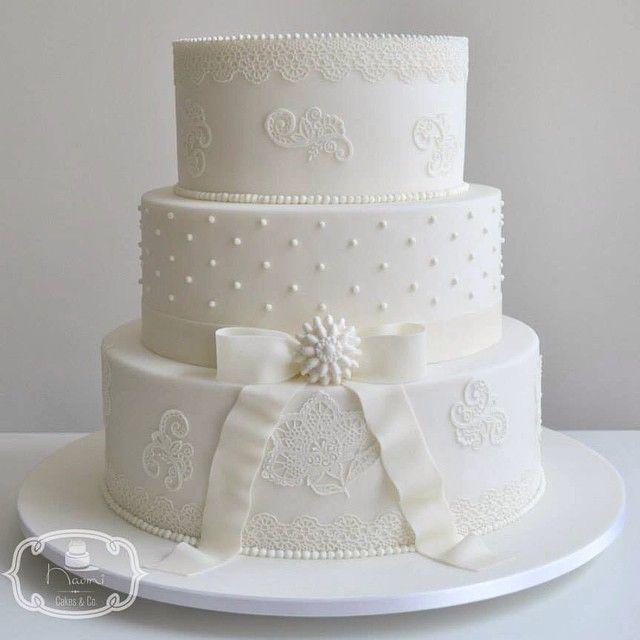Bolo de Casamento: Bolo de 3 andares de Bem Casado coberto e decorado com Pasta Americana. Decoração com laço, broche, poás e rendas.