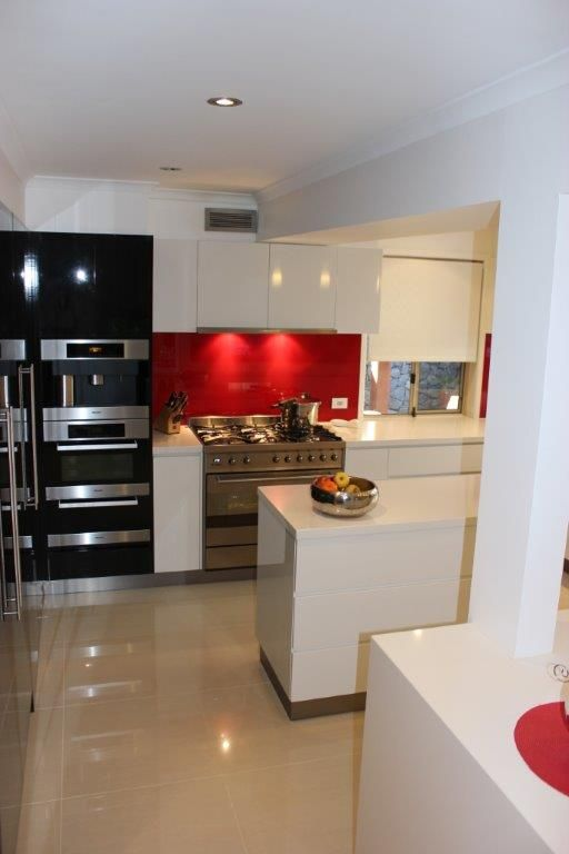 Crisp White Bench Top with Red Splashback - Kitchens Renovations Brisbane