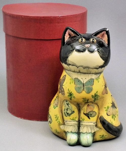 """Joan and David De Bethel - Papier-mache cat with yellow glass eyes, decorated with yellow decoupage cardigan and with six line verse to reverse, 7.25ins high (black painted marks to base - S322HJ and dated 1973 - slight chip to ear), contained in Herbert Johnson """"Cat Box"""""""