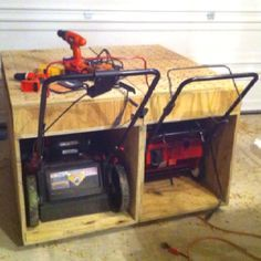 Dual purpose workbench and lawnmower, snow blower storage container. My grandfather built one of these in the 60's, but it was outside, had a little ramp in front, was made just large enough to hold his lawnmower and had a door on the front that had slots in it so it could close and the handle stayed out.