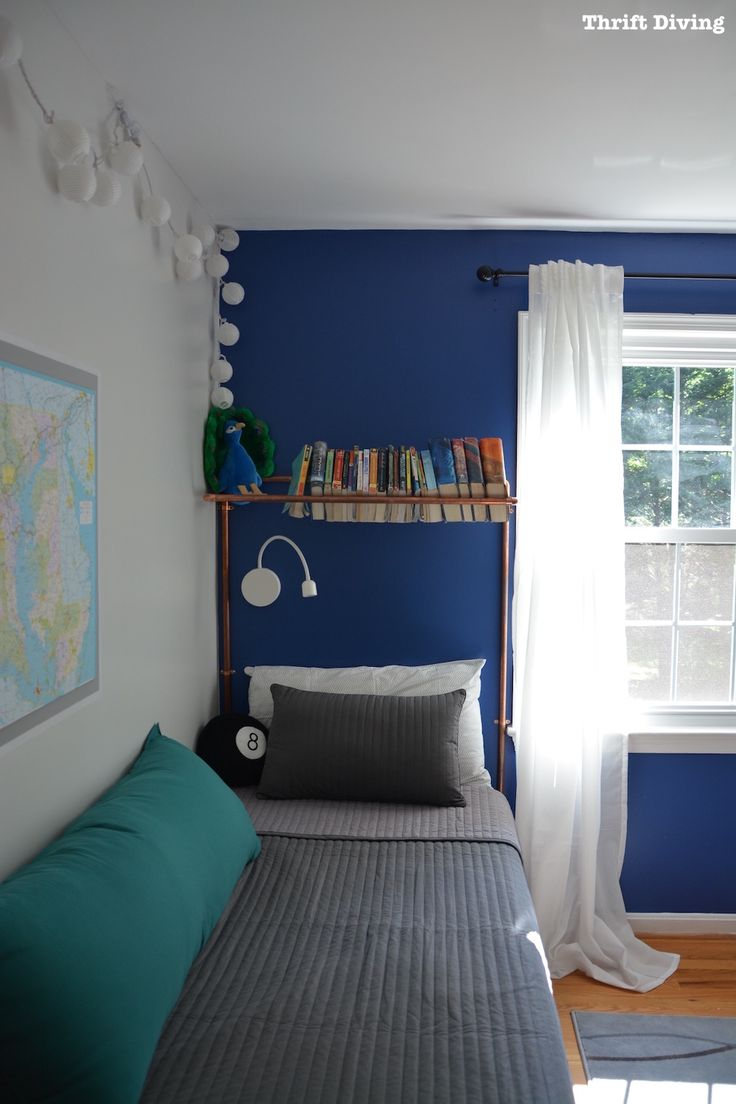 Tween boy bedroom makeover in blue with copper pipe headboard and bookcase