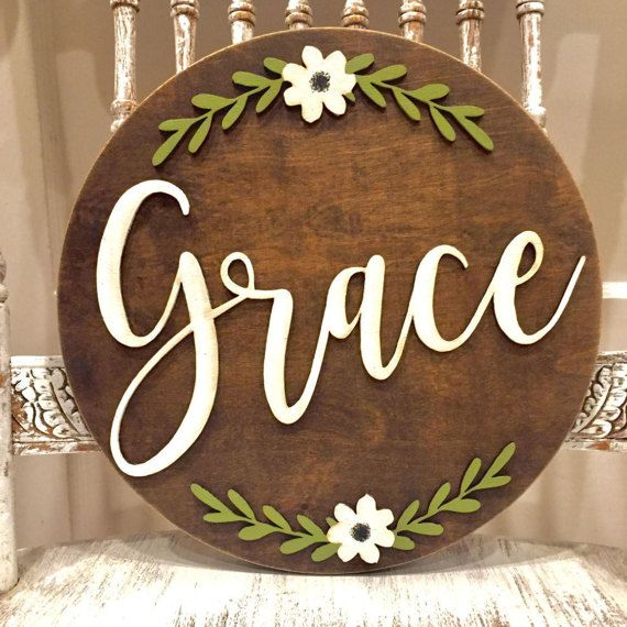 Grace round wood sign with laser cut letters and flower.  Measures 11 1/2 inches. Hardware on back for hanging.