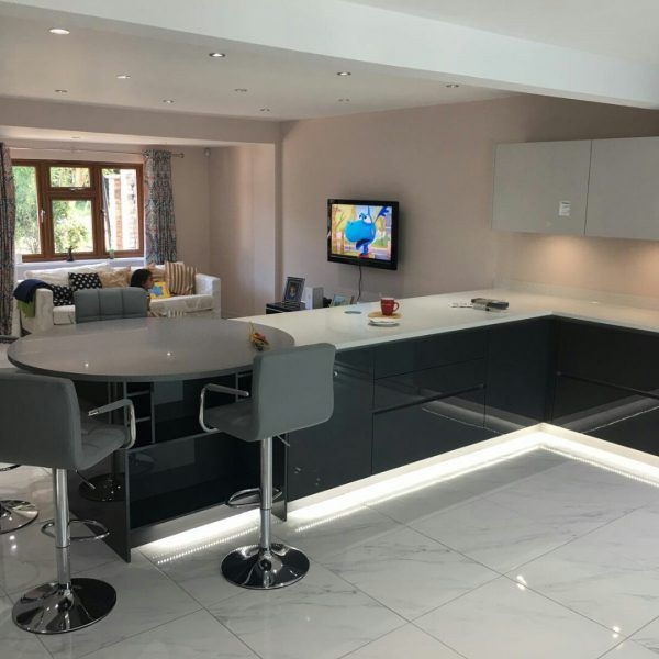 This black and white glossy modern kitchen features the Bianco Stella and the Grigio Scuro Stella. A very unique feature has been put in to this kitchen, a round breakfast bar on the end for the perfect informal meal. It is a modern style kitchen that has been designed by one of our kitchen partners Blax Kitchens.
