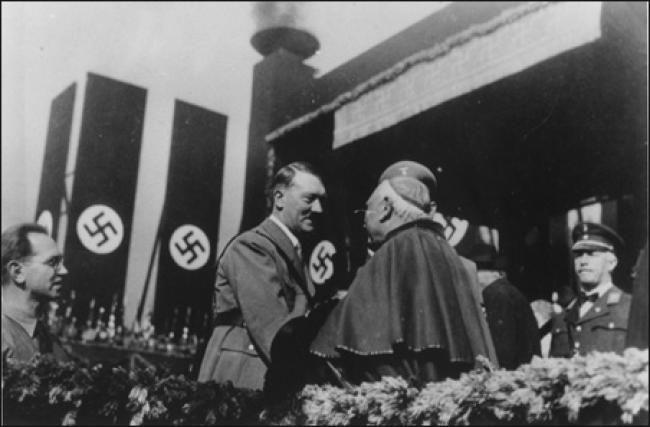 Adolf Hitler greets a Catholic Cardinal at a rally.
