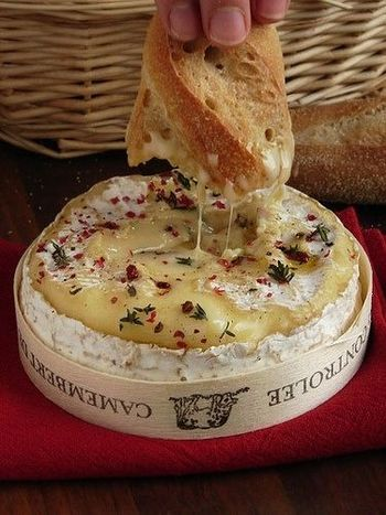 オーブンであぶったカマンベールチーズに、バケットを浸して。 ピンク・ペッパーかパプリカ・パウダー、お好みのハーブで味にアクセントをつけて。