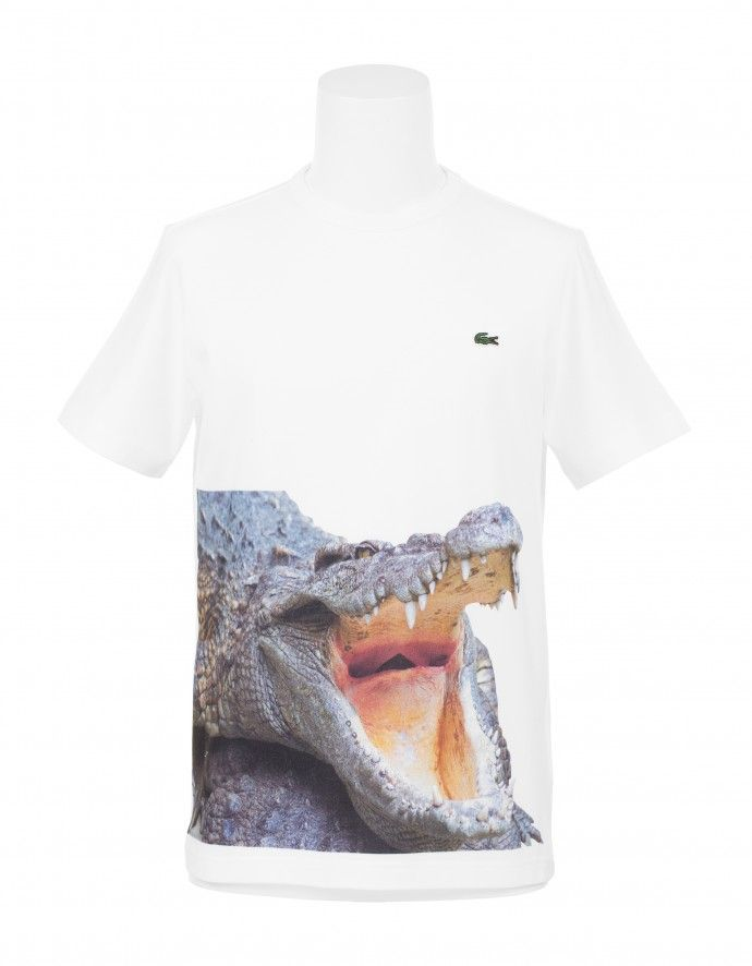 T-shirt Crocodile JUNYA WATANABE x LACOSTE T-shirt Crocodile  Junya Watanabe recently aligned with acclaimed heritage brand Lacoste on a pair of shirt designs. The eccentric Japanese imprint reimagines Lacoste's iconic crocodile logo by applying a printed graphic of the savage creature on the bottom portion of a clean white T-shirt. The second is a traditional polo-style pullover with the activewear brand's trademark emblem landing on the upper left area.