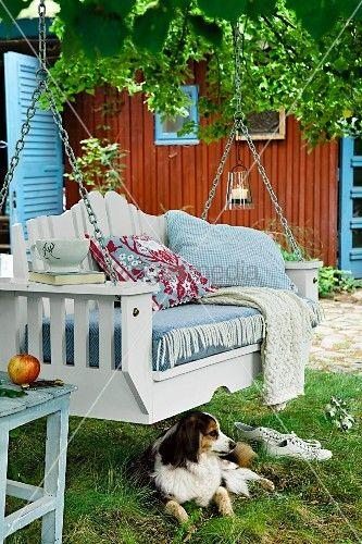 Hund liegt vor Hängebank mit Auflage & Kissen in Garten