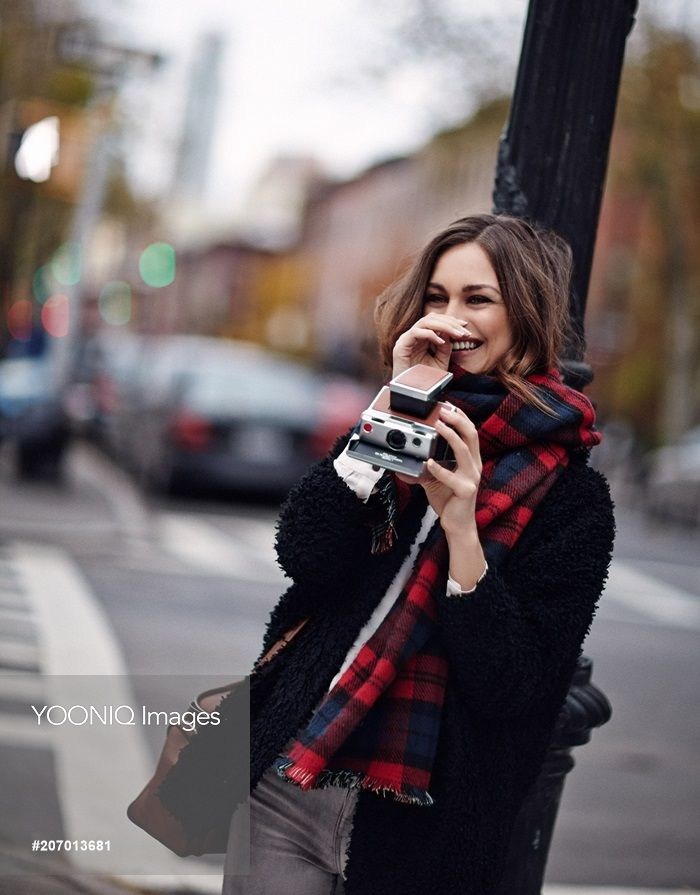 Yooniq images - Girl on street laughing in plaid scarf with vintage camera