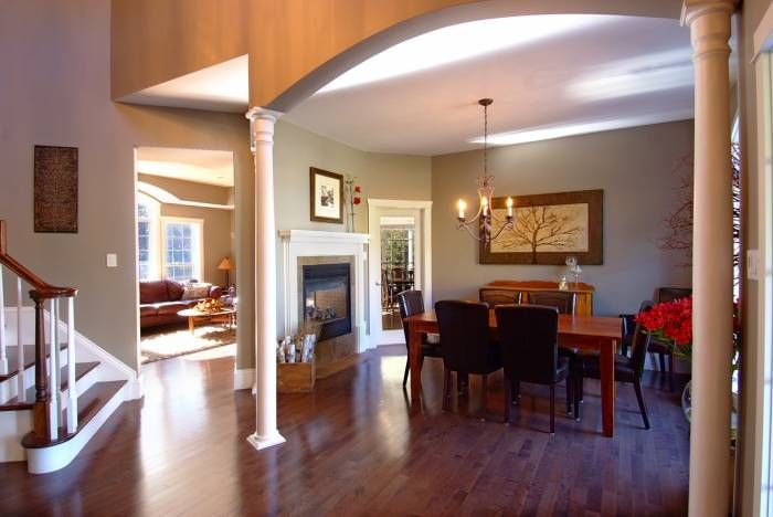 Homes for sale in Carp- Dining Room -Three colonial pillars grace the entry to the formal dining room with a two sided gas fireplace, high ceiling, iron chandelier, hardwood floors and big picture window offering views of the manicured lawns and mature trees.  MLS#887857