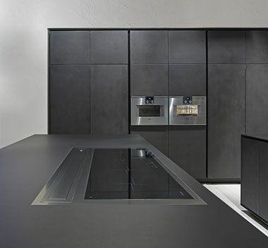 Cucina con isola monolitica in cemento nero: One by Rifra