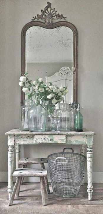 lovely vintage mirror, shabby old table, blue glass and bottles and topped with white flowers xx