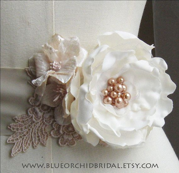 Vintage-inspired wedding sash featuring an ivory bloom with gold pearls, velvet millinery flowers, and tea-stained venice lace on ivory ribbon sash.  Rustic wedding perfection!