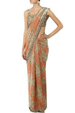 a salmon pink and beige floral printed georgette saree with a gold sequin border. It has bugle beads tasseled hem pallu. It comes along with a gold fully sequined blouse in khadi base. Shop Now at www.carmaonlineshop.com #carma #carmaonlineshop #indian #designer #indianwear #Sabyasachi #ethnicwear #fashion #saree #style #ethnic #shopnow #onlineshopping