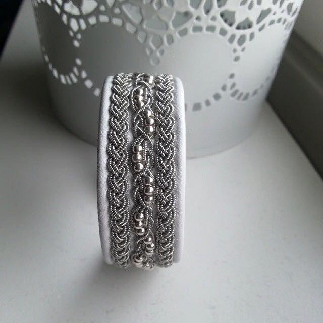 Tenntråd, äkta silverpärlor och en tenn stavs knapp på vitt renskinn.