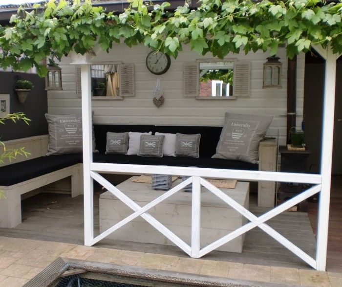 Een Franse feeling in je tuin? Deze witte veranda, afgewerkt met een druivenstruik, geeft je een optimaal Frankrijk-gevoel.