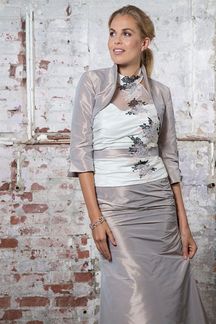 be the light, 1243+39424, collectie 2016 nb. Een mooie set voor de bruid die kiest voor gemak en een kleurtje. De bovenkant van het topje sluit hoog in de hals met organza en laat de schouders vrij. Het wordt opgefleurd met zwart/grijze bloemapplicaties. De gekleurde rechte rok maakt iets moois van het geheel. Bijpassend een bolerootje in dezelfde kleur als de rok. #gekleurd #organza #koonings
