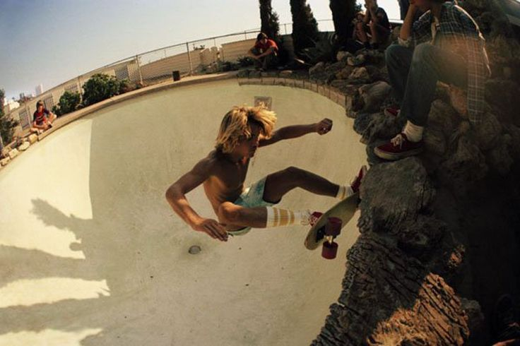 1970s style skateboarding -- note the Vans, tube socks, skinny wooden board, and the absence of helmets knee pads, and other body armor...Droughts and a bad economy in southern California meant vacant houses and empty swimming pools -- skate parks before anyone knew what that was. Photograph by Hugh Holland