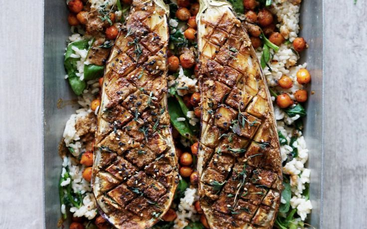 Eggplant is cut in half, brushed with miso, baked, and then laid over a bed of rice, chickpeas, and wilted spinach.