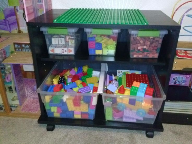 DIY Lego Table!  TV cart w/ Lego Duplo mat attached with small wood screws. Large bins are permanently attached with wood screws, nut/bolt in the middle to keeps bins from slipping, and middle top with white duct tape to keep fingers from being pinched. The wheels on cart make moving from room to room easy.