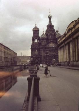 Foto antigua de La Iglesia del Salvador de San Petersburgo, de 1963, mientras una mujer barre la acera