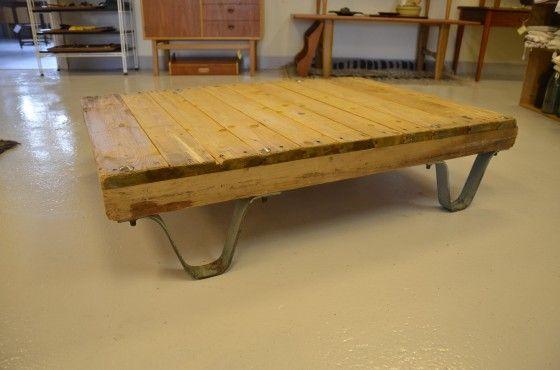 Lågt soffbord i industristil med kraftig patina.  Gammal industripall med skiva i spontat virke och ben i bockade plattjärn.  100x80x25cm