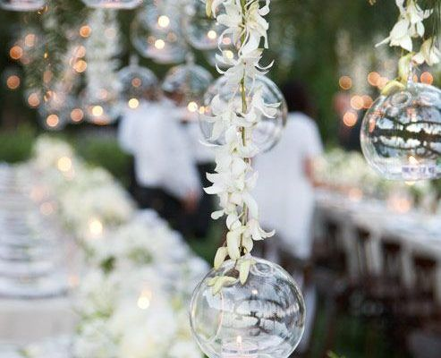 glass bubbles with a single tealight in each brighten this outdoor wedding reception space