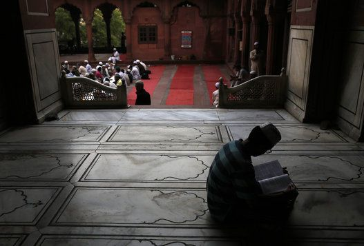 Beautiful Ramadan Photos From Around The World - An Indian Muslim reads holy book as others wait to break fast on the first day of the holy month of Ramadan at the Jama Mosque in New Delhi, India