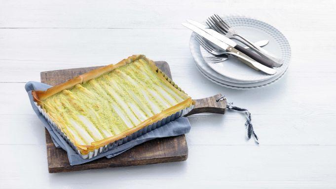Deze hartige taart kun je zo op een feestje serveren, zo mooi ziet hij eruit. Je maakt de taart al binnen een half uur, daarna laat je de oven het werk doen. Asperges schillen Verwarm de oven voor op 200 graden. Schil 1 kilo witte asperges rondom met een dunschiller vanaf vlak onder het kopje naar beneden en verwijder de houtachtige onderkant. Kook de asperges 10 minuten. Neem ze met een schuimspaan uit de pan en laat goed uitlekken. Filodeeg Smelt ondertussen 25 gram boter in een steelpan…