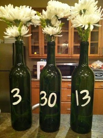 Recycled wine bottles with the wedding date added ready to be filled with flowers or candles.  See more bridal shower decorations and party ideas at www.one-stop-party-ideas.com