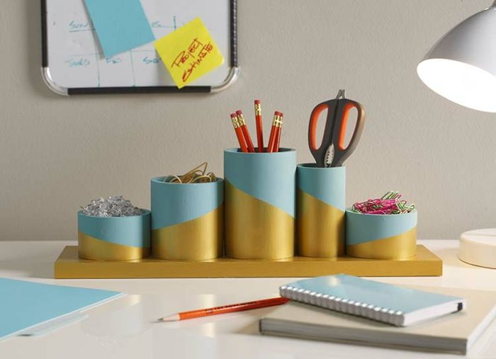 step dad gift ideas, light blue and gold office supplies organizer with pins, rubber bands, pencils, scissors and paper clips, on an office desk with notepads and a lamp