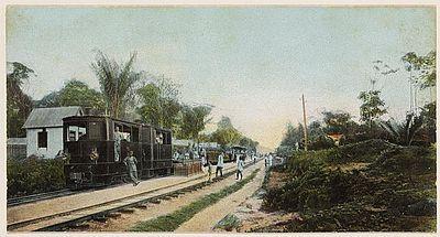 Spoorweg met trein in Lelydorp, voorheen Koffiedjompo, bij Paramaribo, omstreeks 1920