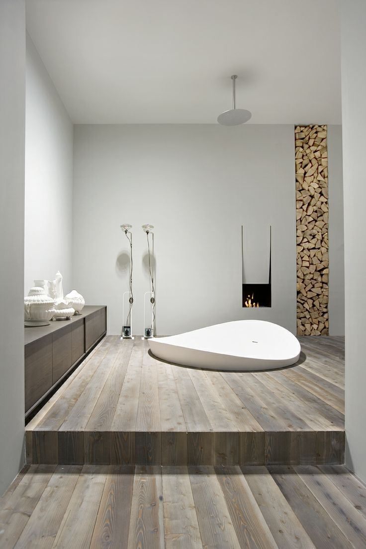Mmmmm this white contemporary bathroom feels so serene...The modern sleek and curved bathtub paired next to the light colored hardwood floors would be a perfect look for a spa too!
