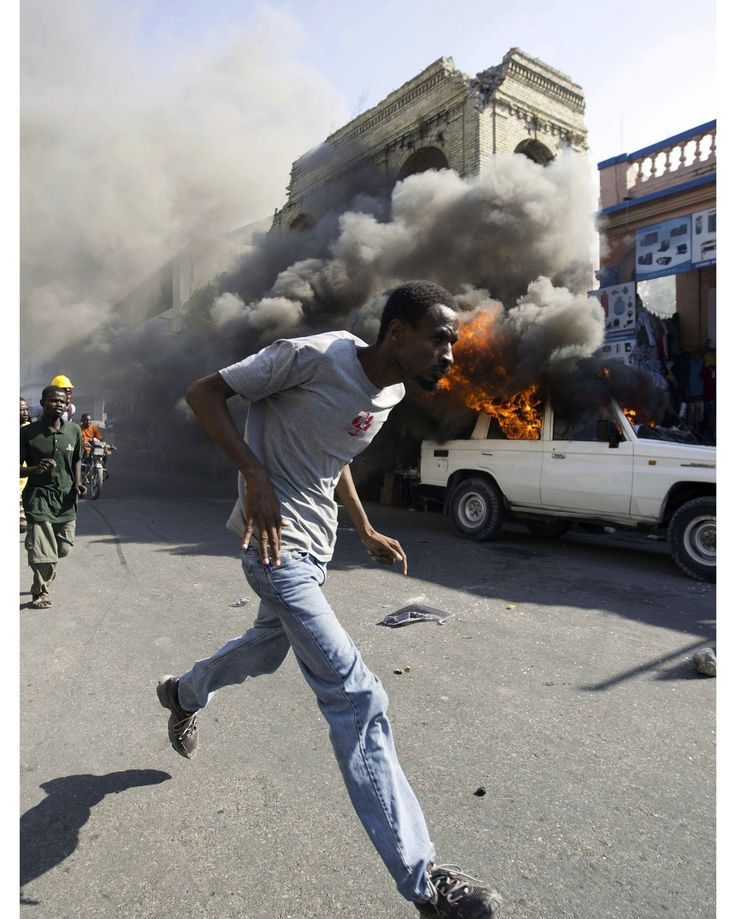 {English below} Un manifestant passe devant une voiture en feu lors d'un rassemblement contre le gouvernement du président Michel Martelly pour exiger l'annulation des prochaines élections du 24 janvier à Port-au-Prince Haïti lundi 18 janvier 2016. Les résultats contestés du premier tour ont engendré de nombreuses accusations de fraudes par les groupes d'opposition et les observateurs. #Photo: Chery Dieu-Nalio -@dieunalio- pour @ap.images - A #protester runs past a burning car during a…