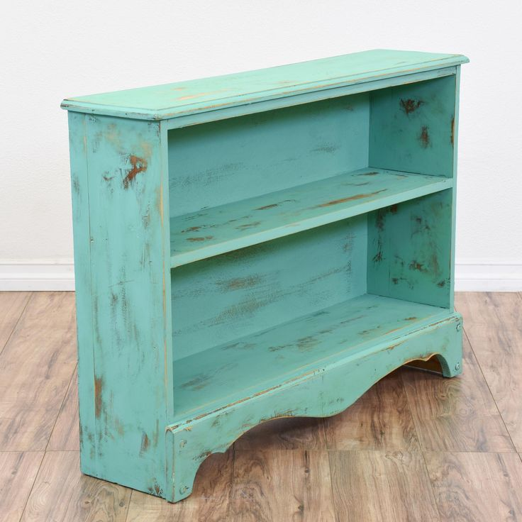 This shabby chic bookcase is featured in a solid wood with a distressed teal blue chalk paint finish. This short bookshelf is in great condition with 1 shelf tier, curved base trim and carved edges. Perfect for displaying books and toys in a kids space! #shabbychic #storage #bookcase&shelving #sandiegovintage #vintagefurniture